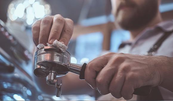Mand gør en espressomaskine ren