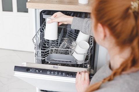 Rødhåret kvinne som legger kruset i en oppvaskmaskin