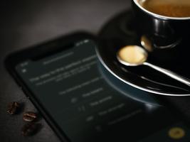 En svart kopp kaffe er på en mobil