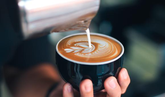 Person holder en kop kaffe og hælder mælk i