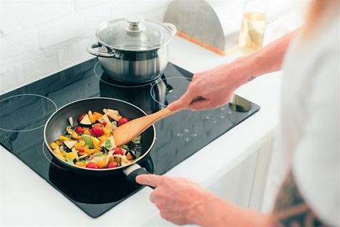 Kvinne som gir mann i en panne på en kokeplate