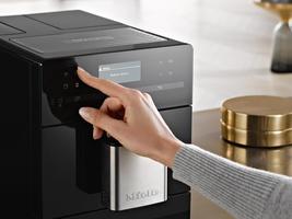 Kvinne velger kaffeprogram på en Miele espressomaskin
